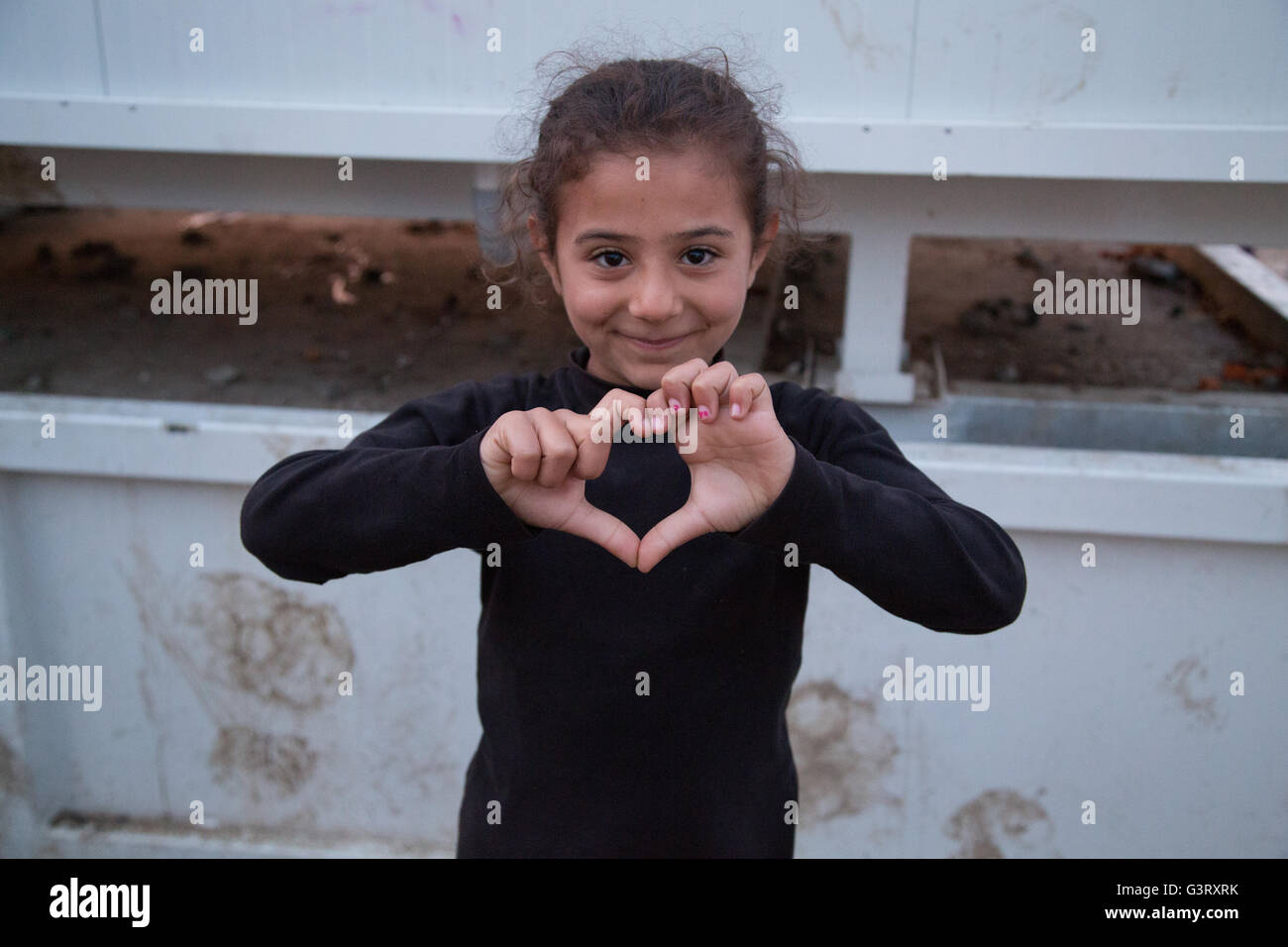 Young Syrian girl in the Idomeni refugee camp makes the shape of a heart with her hands. - Stock Image