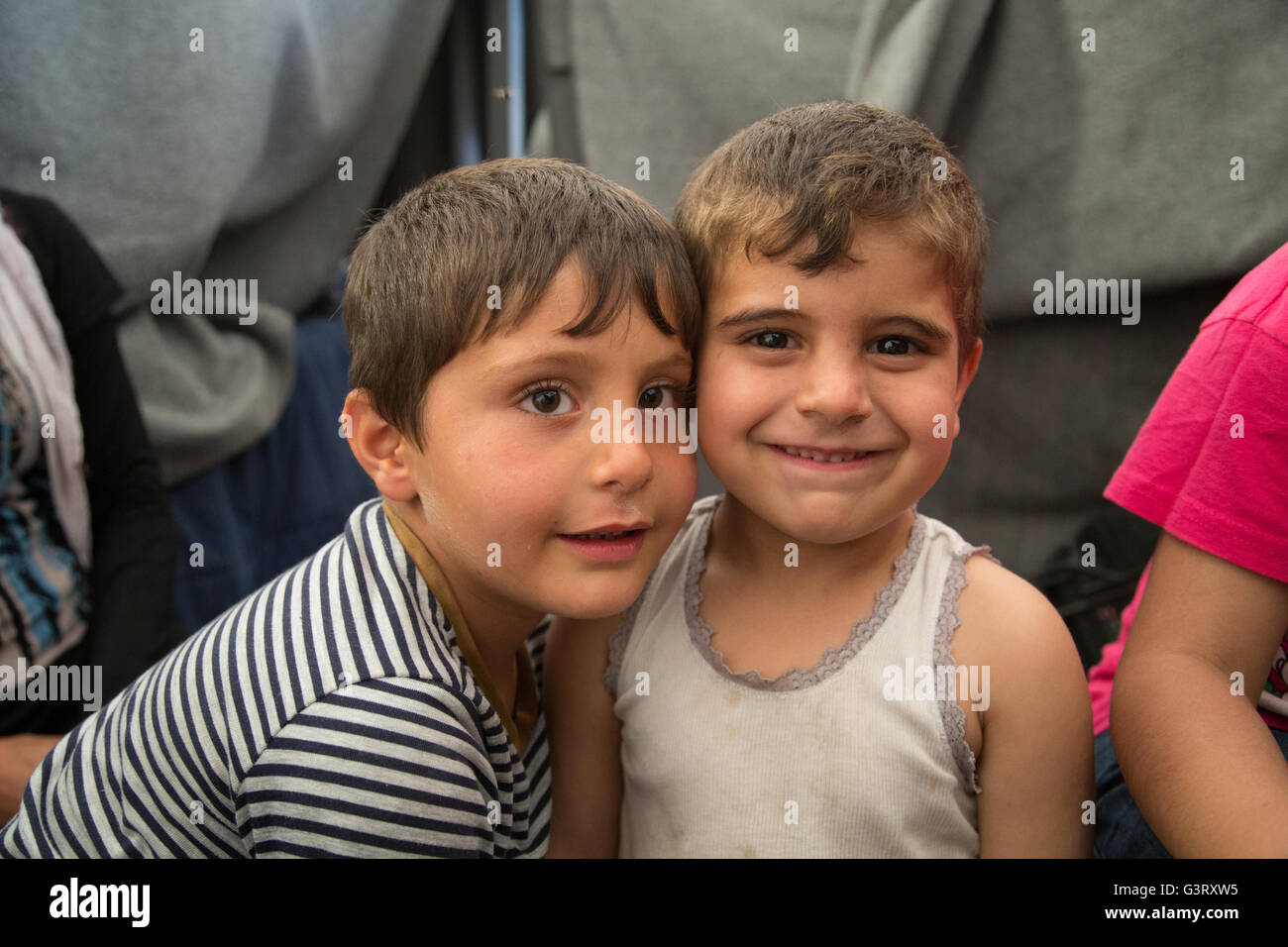 Syrian refugee children smile for the camera in the Idomeni camp at the border of Greece and Macedonia. - Stock Image