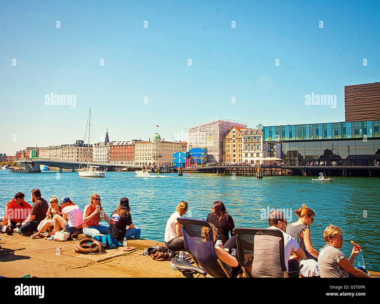 Copenhagen - people enjoy the beautiful weekend weather on the waterfront of Trangravsvej, eating outside the street - Stock Image