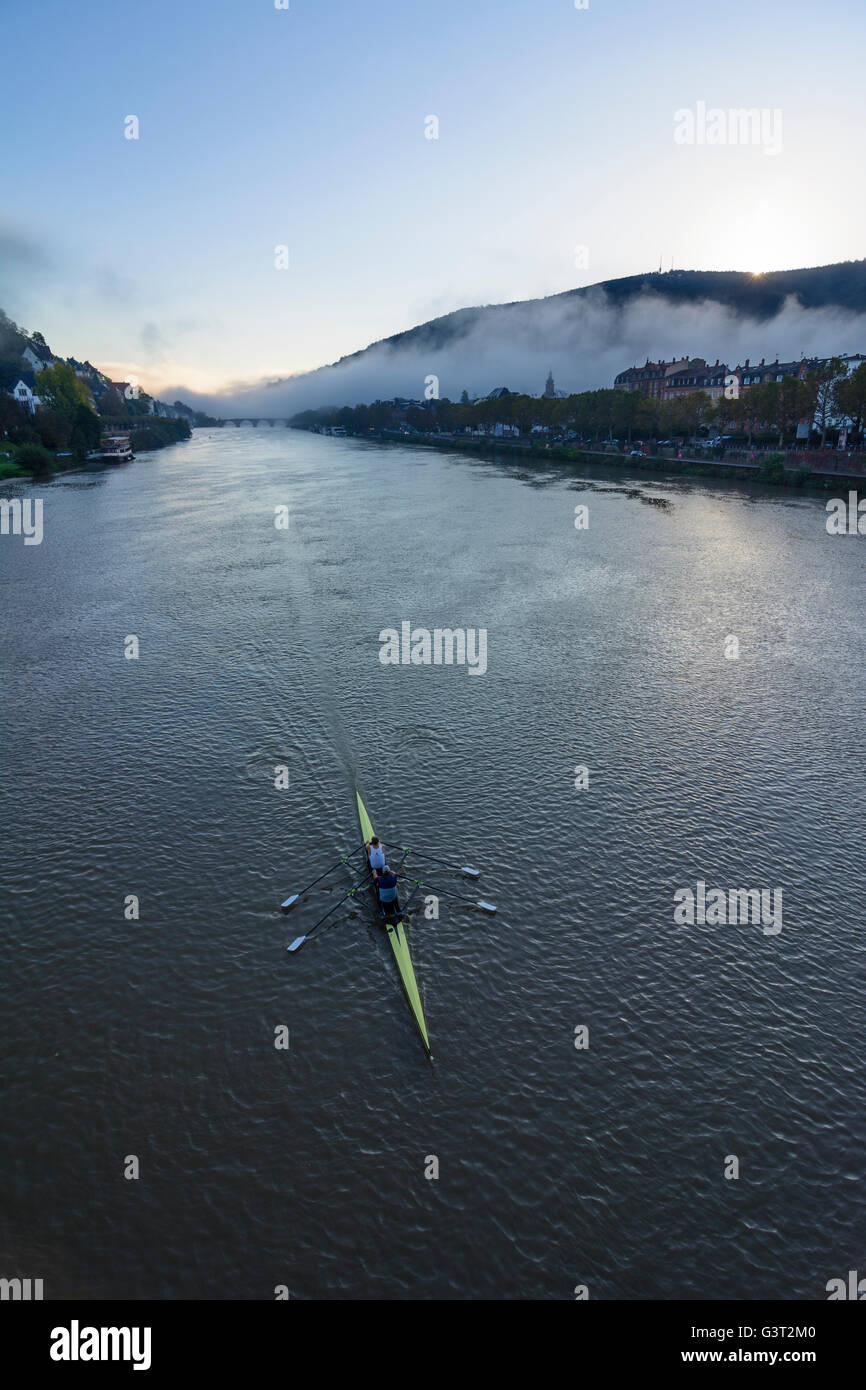 Neckar at sunrise and morning fog with a rowing boat , overlooking the old town and to the Königsstuhl, Germany, - Stock Image