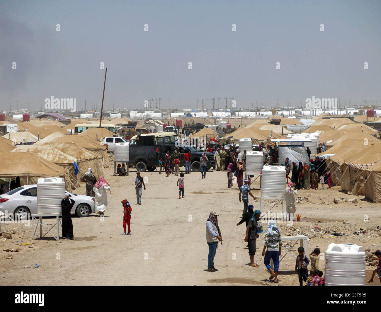Fallujah. 14th June, 2016. People walk outside their tents in a camp for the Internally Displaced People (IDPs) - Stock Image