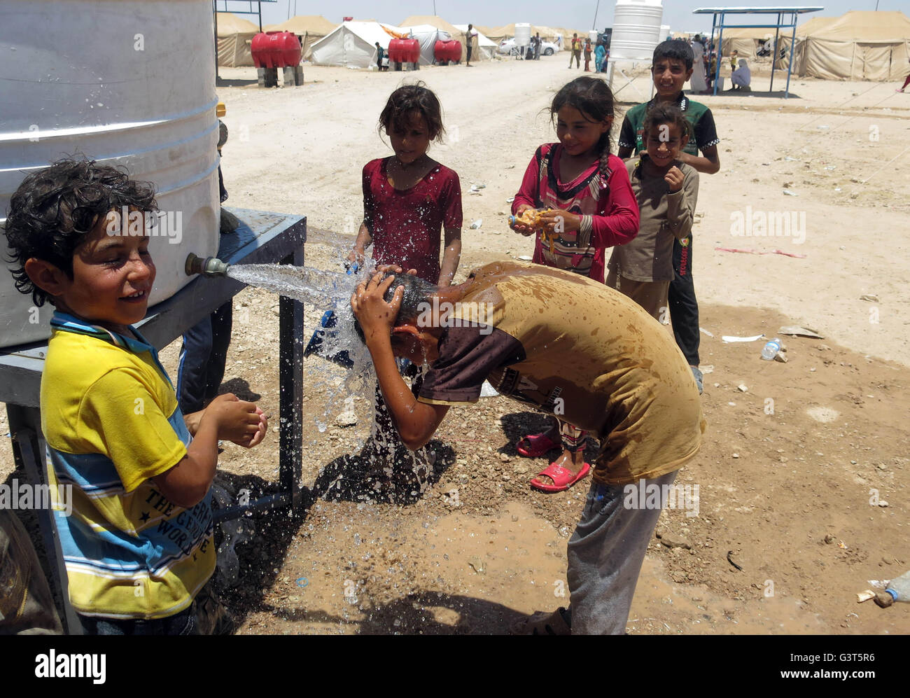 Fallujah. 14th June, 2016. A boy takes a bath by a water tank in a camp for the Internally Displaced People (IDPs) - Stock Image