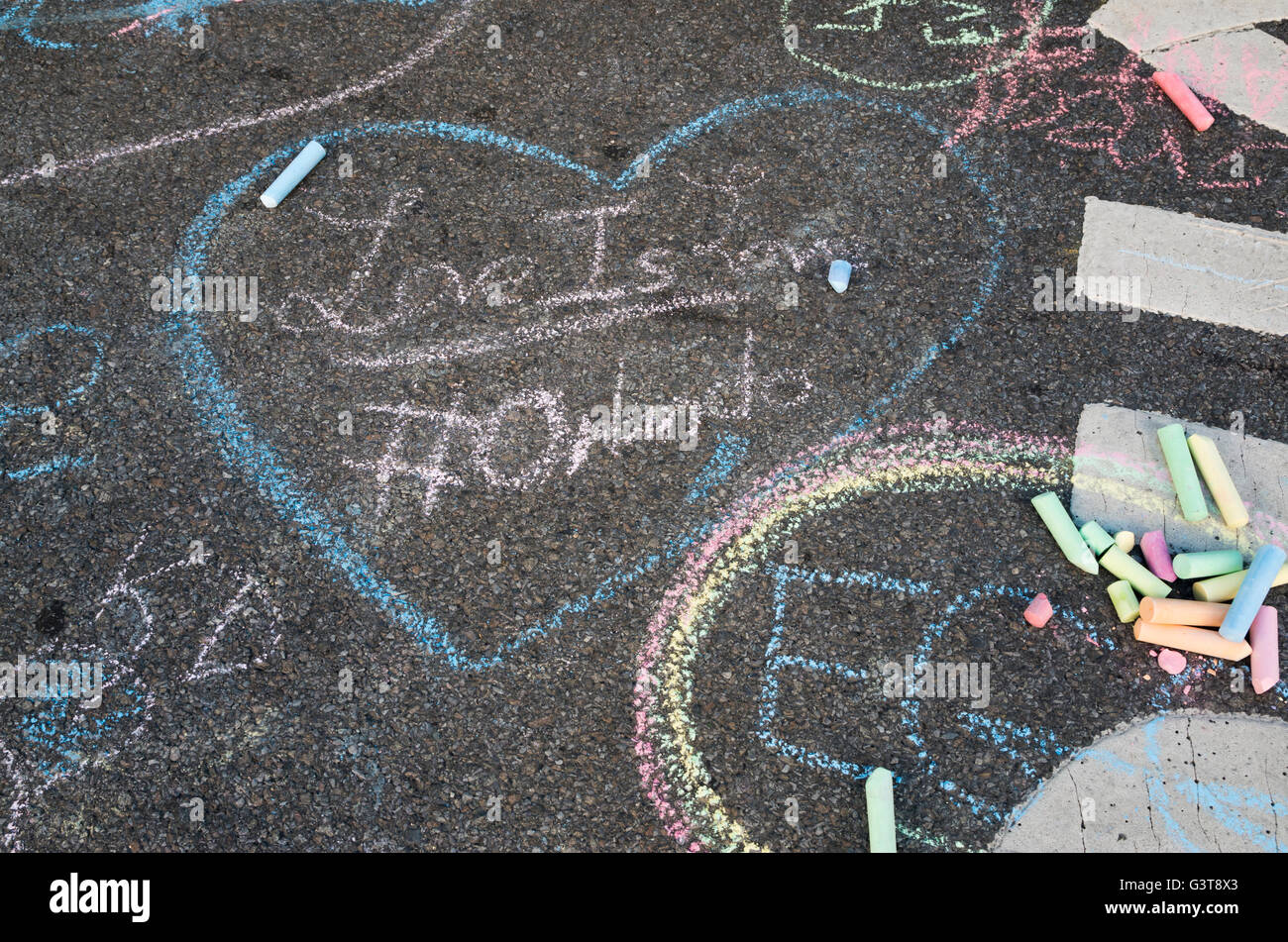 Chalk drawing on road tarmac of heart with Love Is Love #Orlando in tribute to the 2016 shootings. - Stock Image