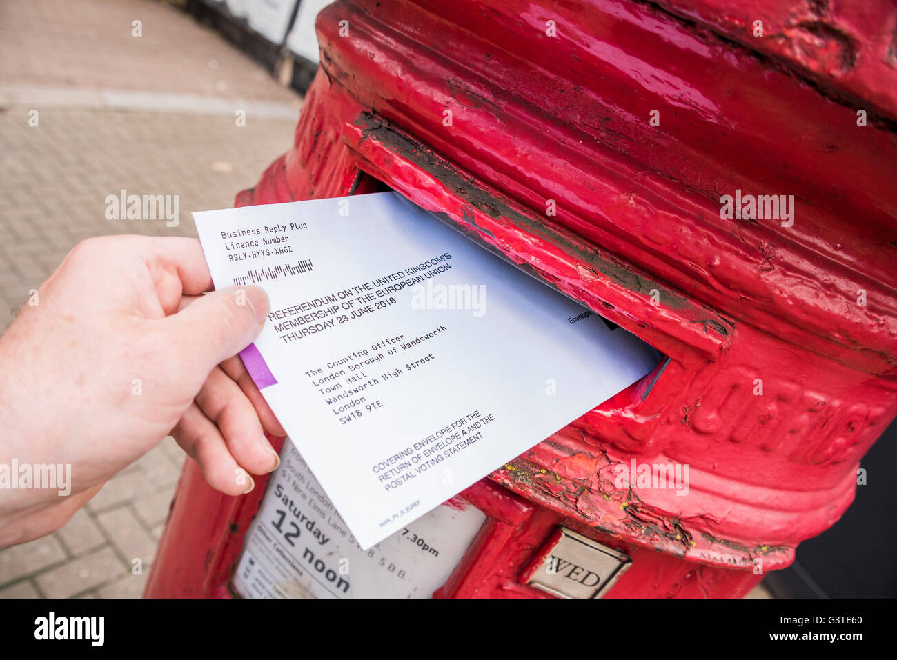 London, UK. 15th June, 2016. Posting a vote for the EU referendum in a traditional red letter box. Credit:  Guy - Stock Image
