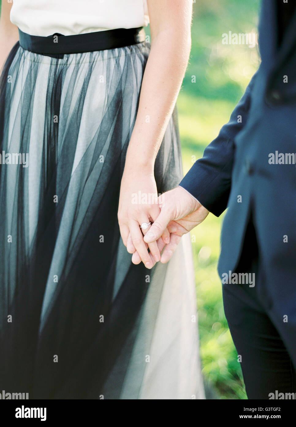 Sweden, Bride and groom holding hands - Stock Image