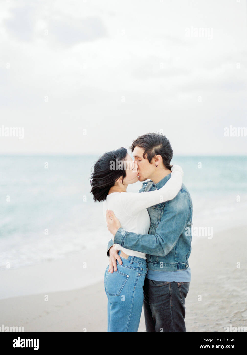 Spain, Valencia, Couple embracing and kissing on beach - Stock Image