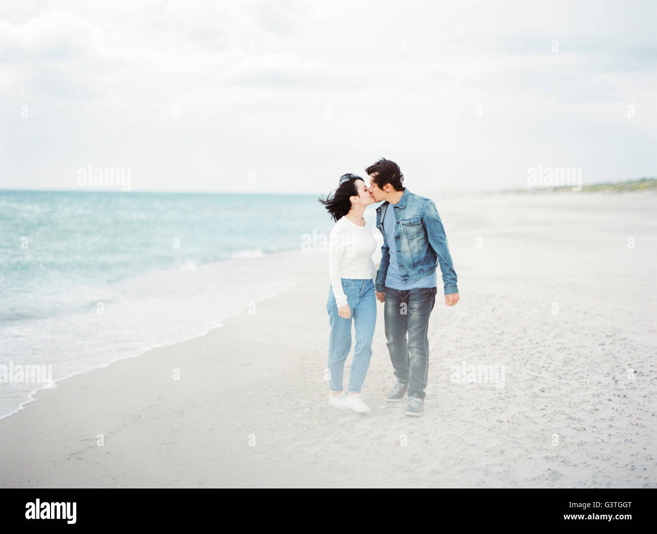 Spain, Valencia, Couple kissing on beach - Stock Image