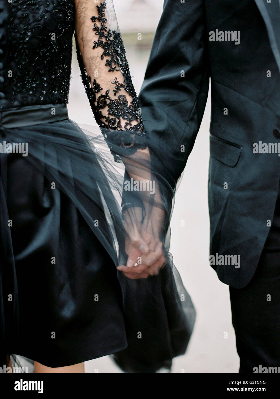 Sweden, Young formally dressed couple holding hands - Stock Image