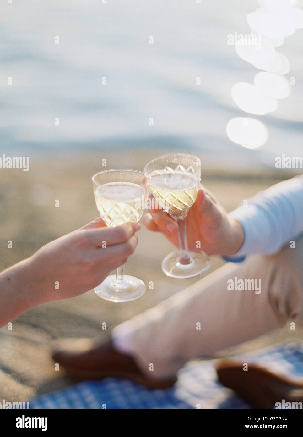 Sweden, Bohuslan, Fjallbacka, Couple toasting with glasses of champagne on sandy beach - Stock Image
