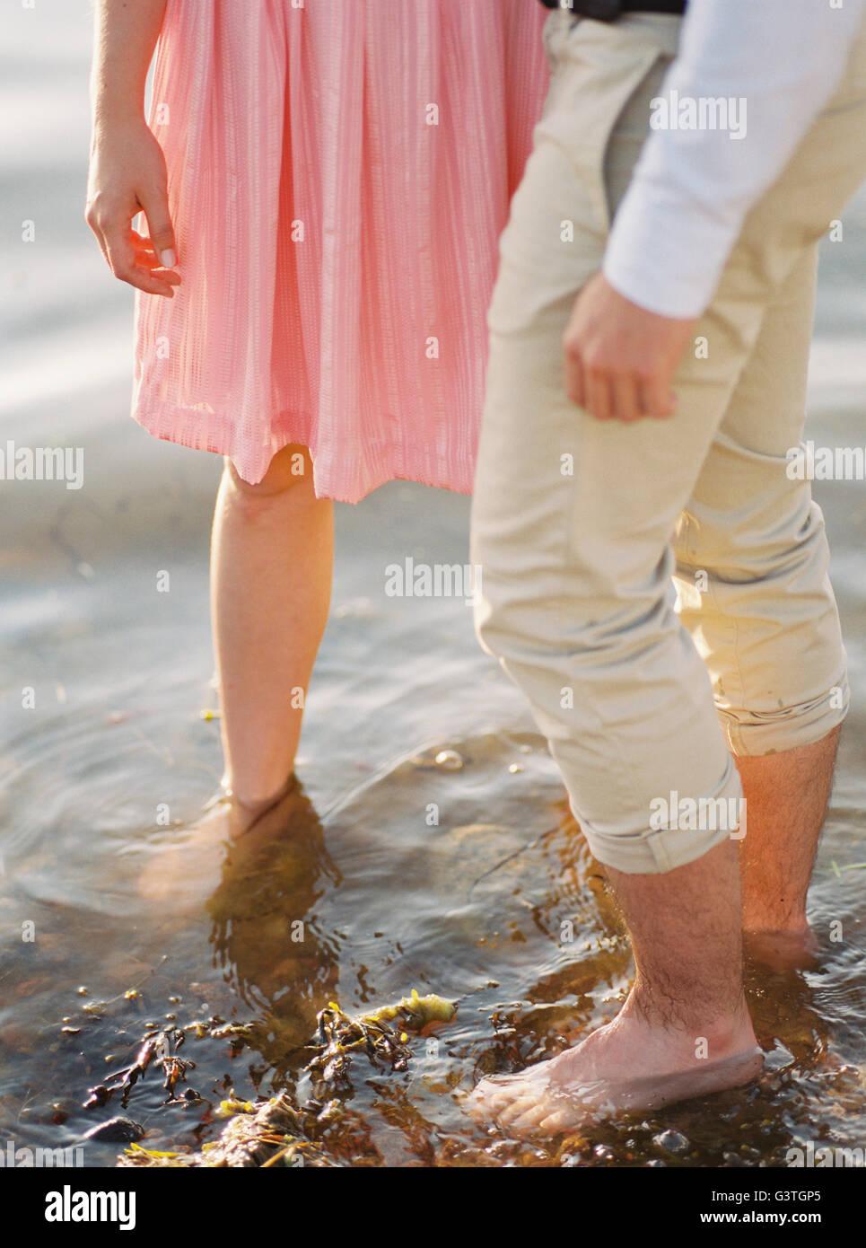 Sweden, Bohuslan, Fjallbacka, Couple standing barefoot in water - Stock Image