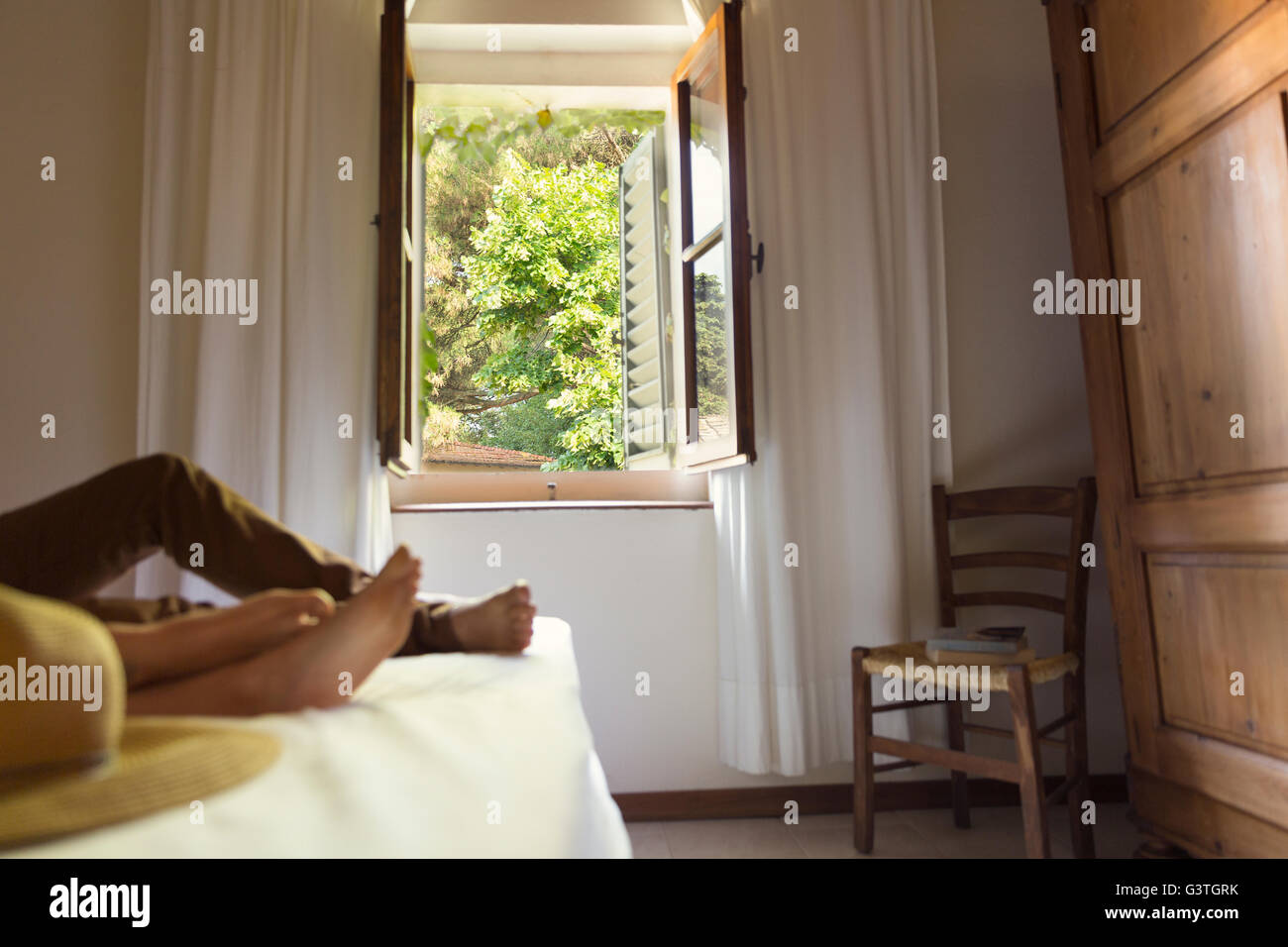 Italy, Couple lying on bed in farmhouse - Stock Image