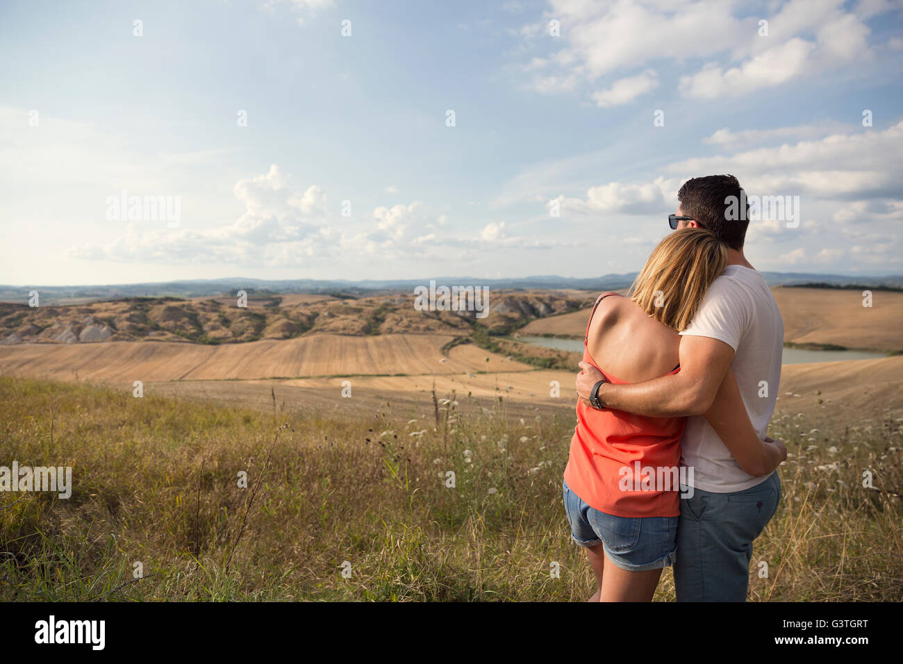 Italy, Tuscany, Hugging couple looking at field landscape - Stock Image
