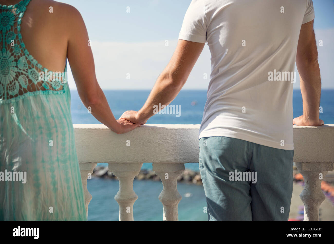 Italy, Cinque Terra, Monterosso, Couple standing on balcony with sea view and holding hands - Stock Image
