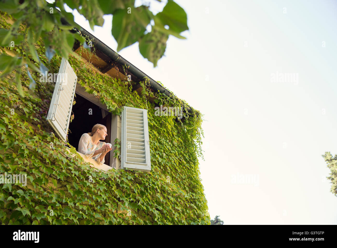 Italy, Tuscany, Dicomano, Woman looking out from window of overgrown house - Stock Image