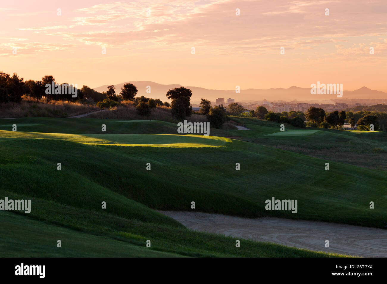 Spain. Barcelona, Real Club de Golf El Prat, Grassy hills of golf course in shadow with distant cityscape in background - Stock Image