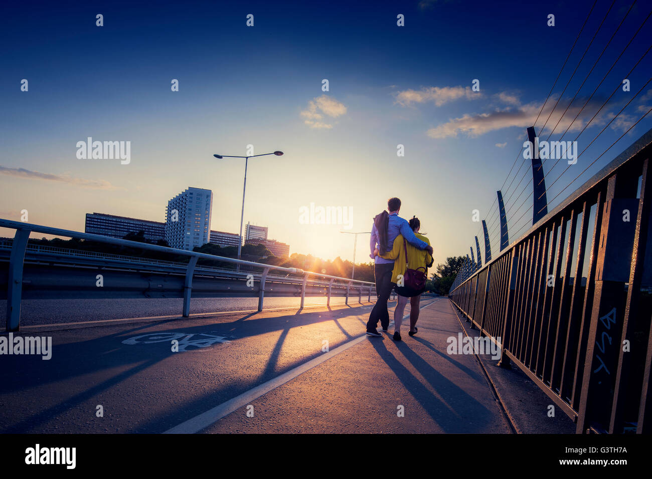 Sweden, Stockholm, Couple walking on bridge - Stock Image