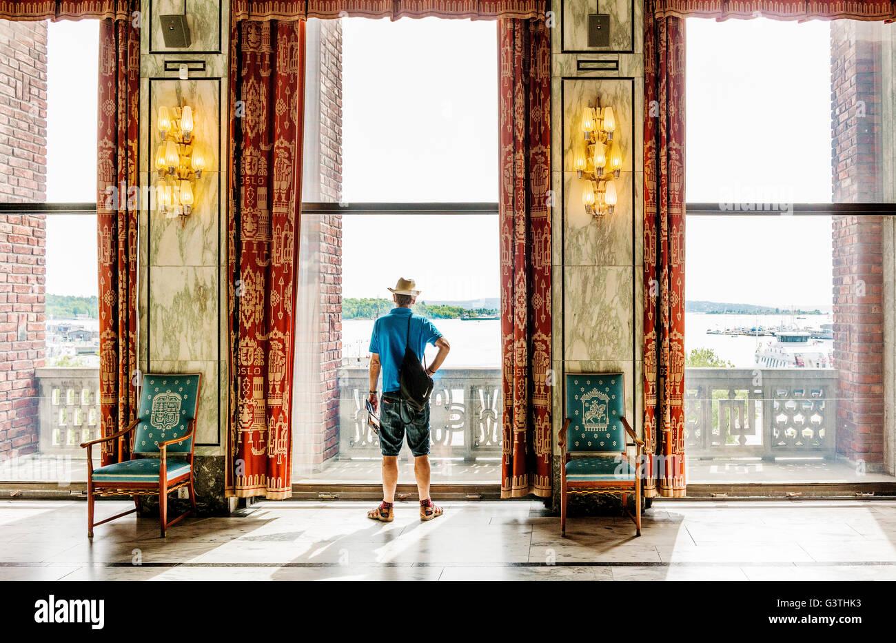 Norway, Oslo, Oslo City Hall, Tourist looking through window - Stock Image