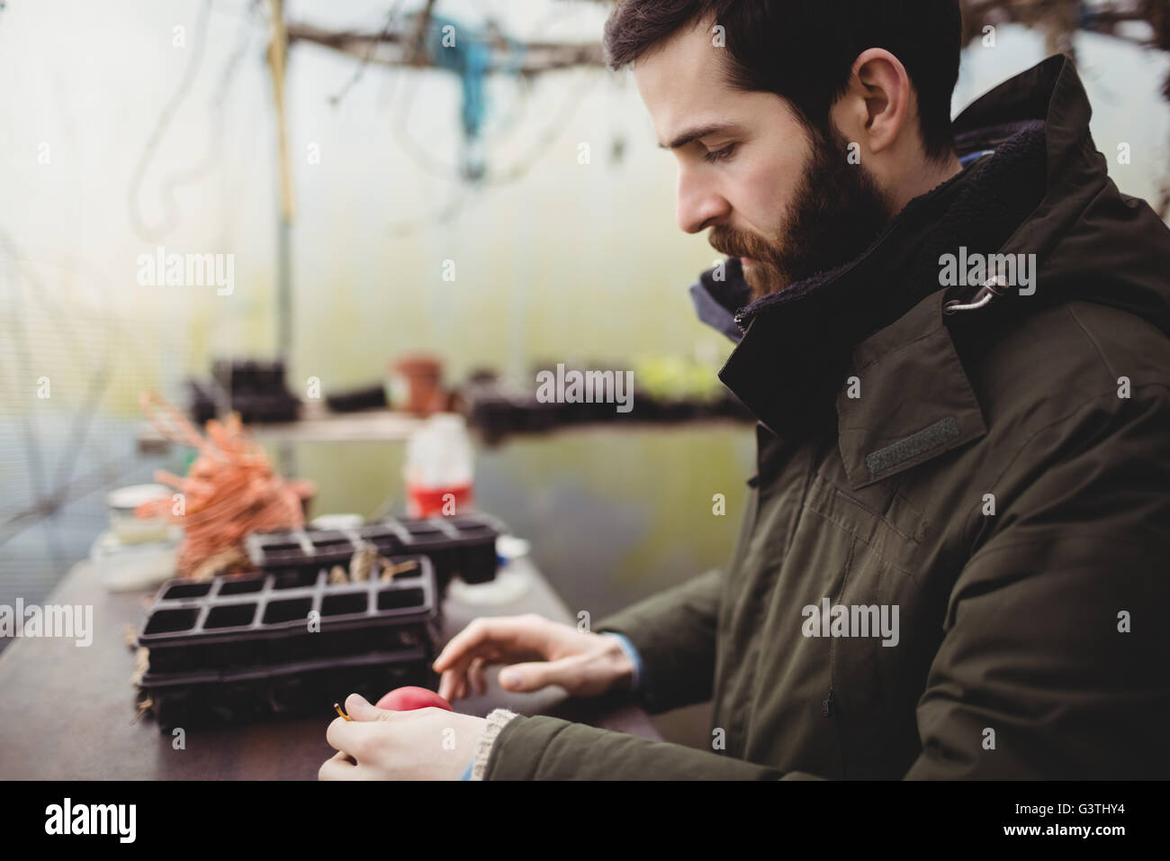 Profile view of hipster man gardening - Stock Image