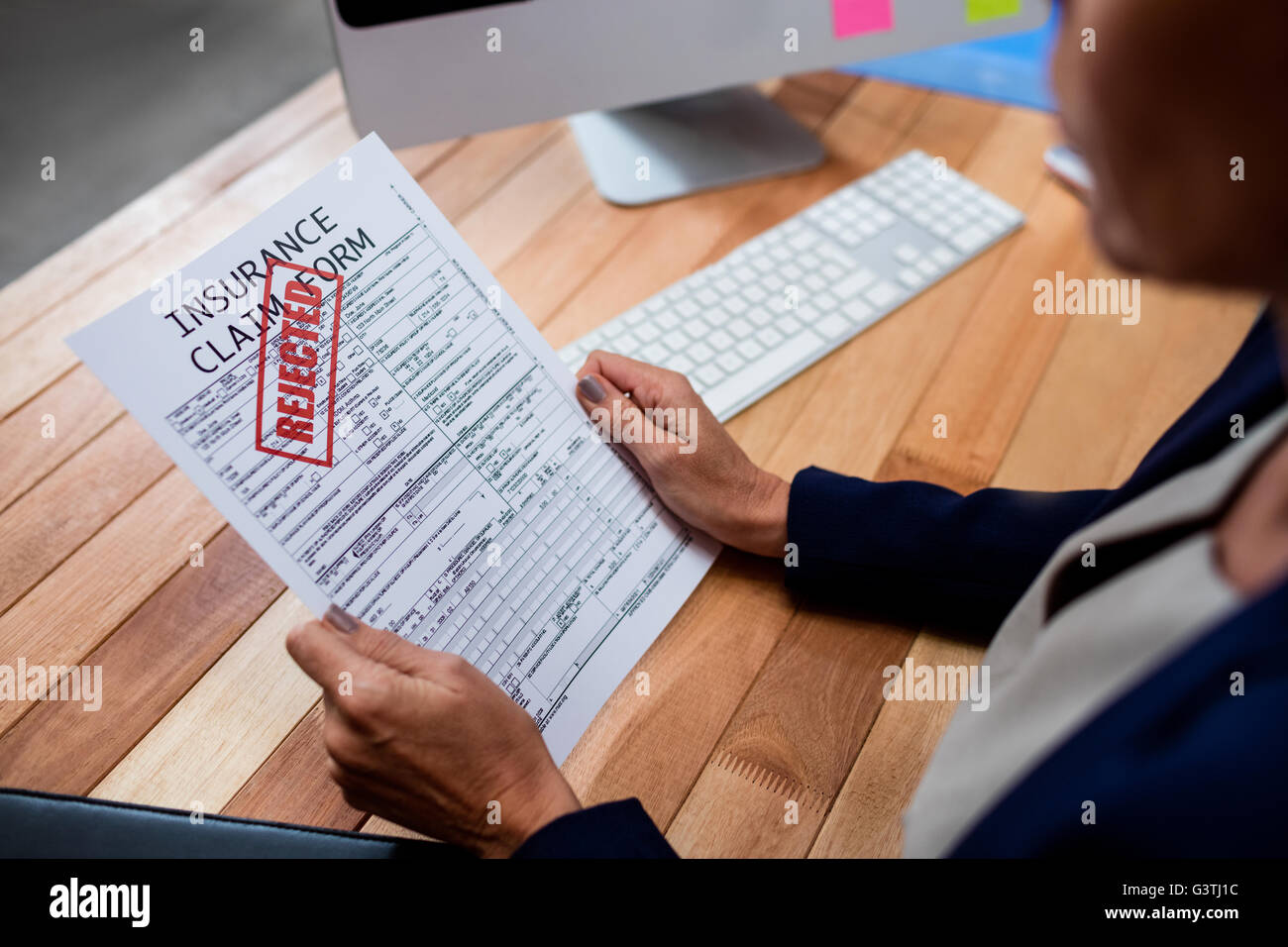 People reading an insurance claim form - Stock Image