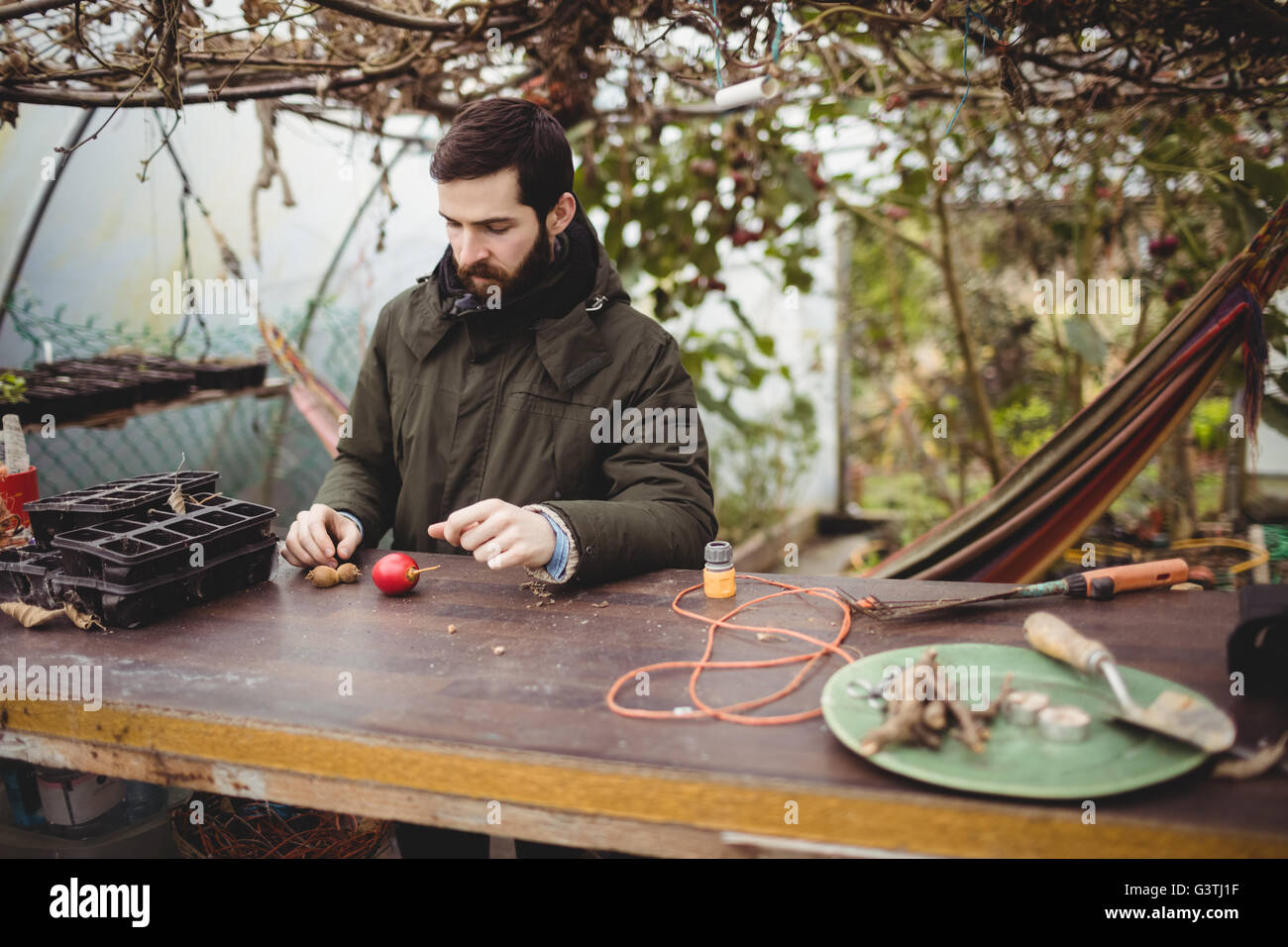 Hipster man sitting and gardening - Stock Image
