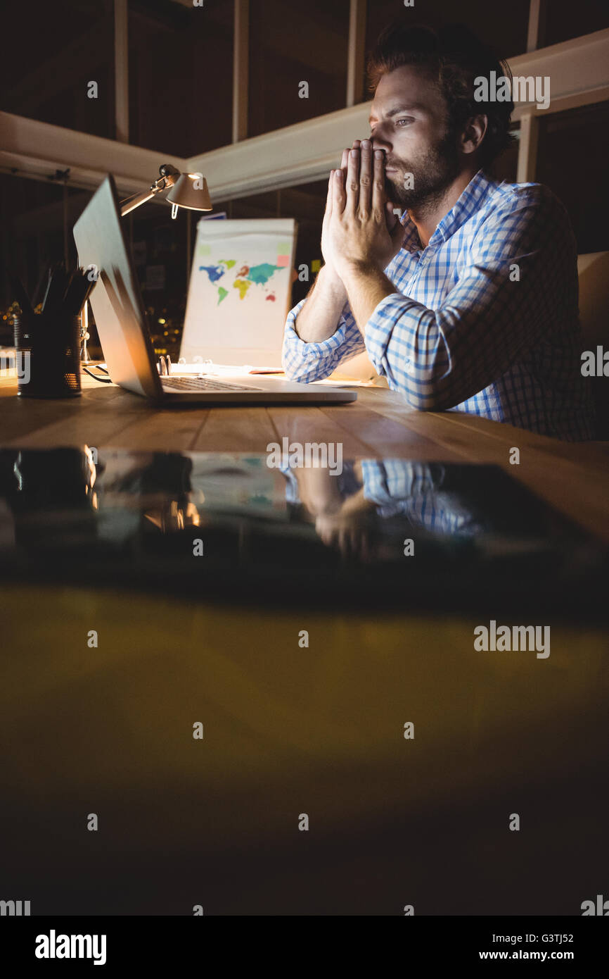 Overworked businessman working at night - Stock Image