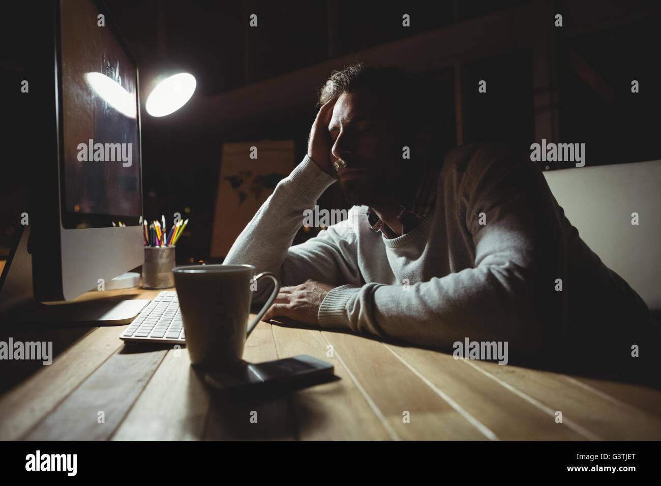 Sleepy businessman watching his computer - Stock Image