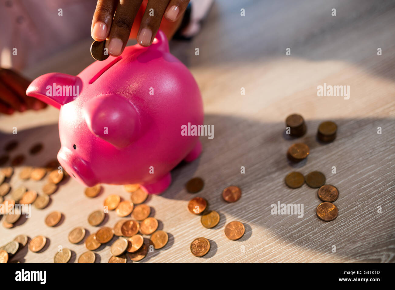 Hand putting money in a piggy bank Stock Photo