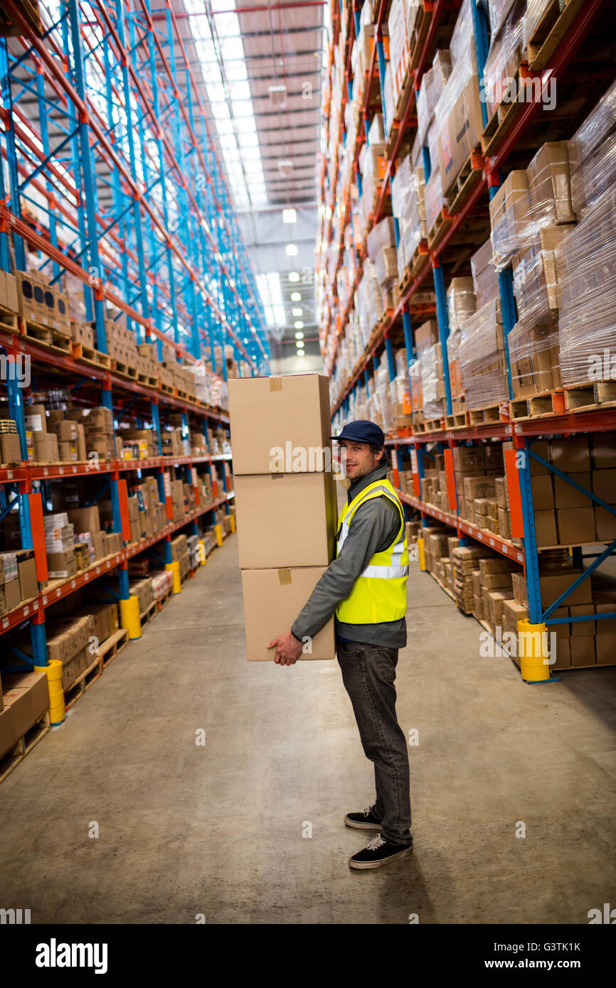 Warehouse worker carrying boxes - Stock Image
