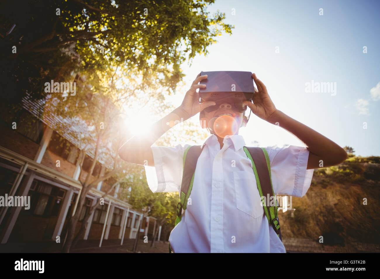 School boy in virtual reality glasses in campus - Stock Image