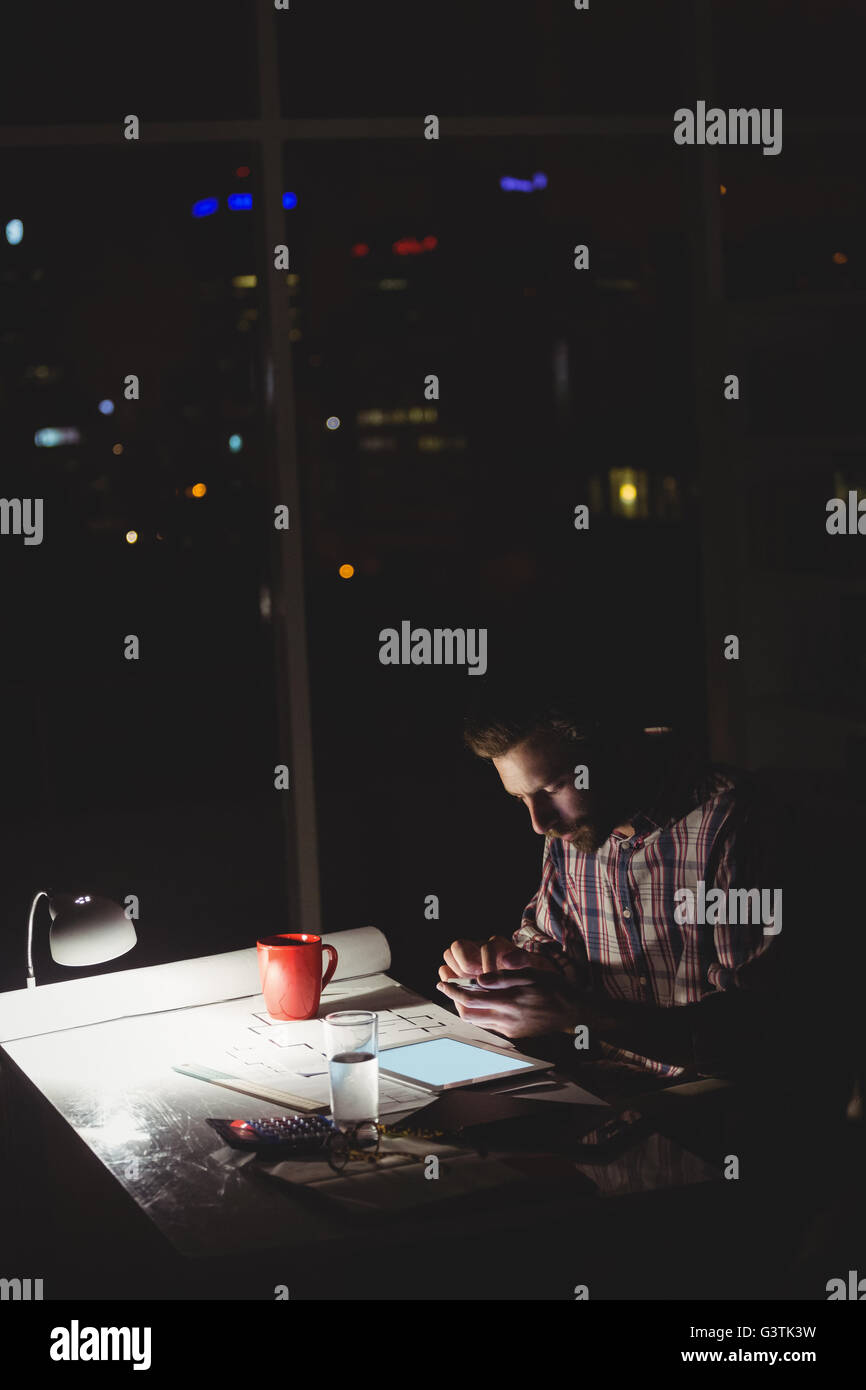 Hipster using a smartphone and a tablet computer in darkness - Stock Image