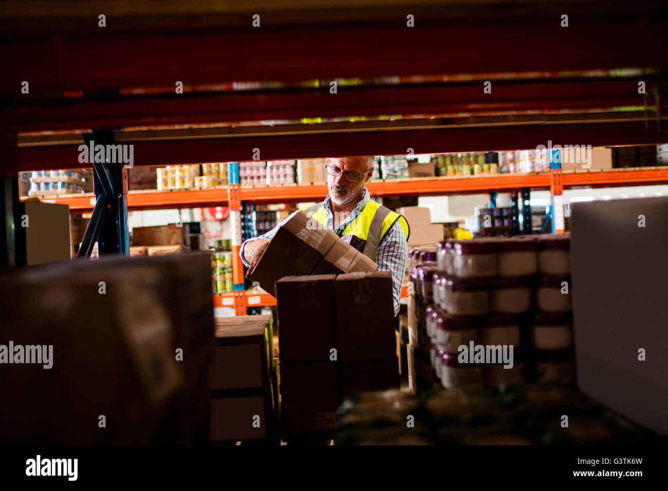 Warehouse worker tidying the shelves - Stock Image