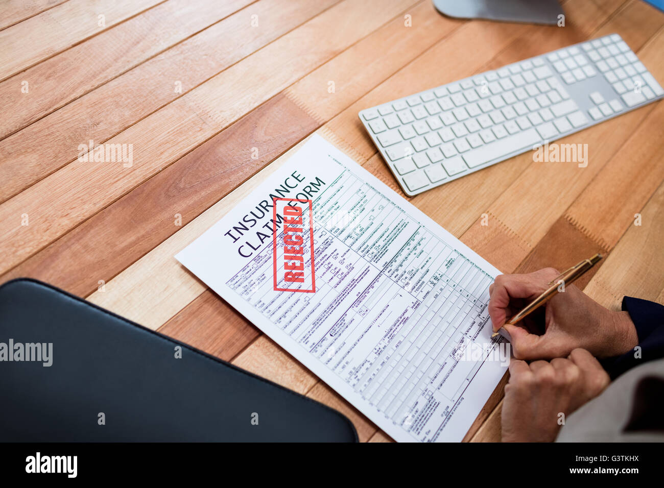 Hand writing on an insurance claim form - Stock Image