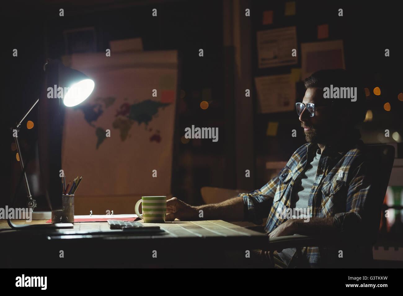 Businessman working at night - Stock Image