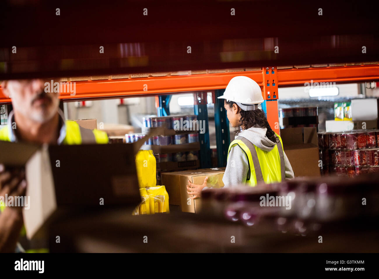 Workers warehouse tidying the shelves - Stock Image