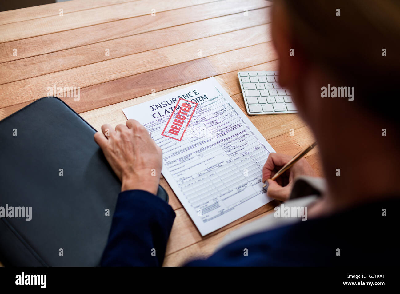 People writing on an insurance claim form - Stock Image
