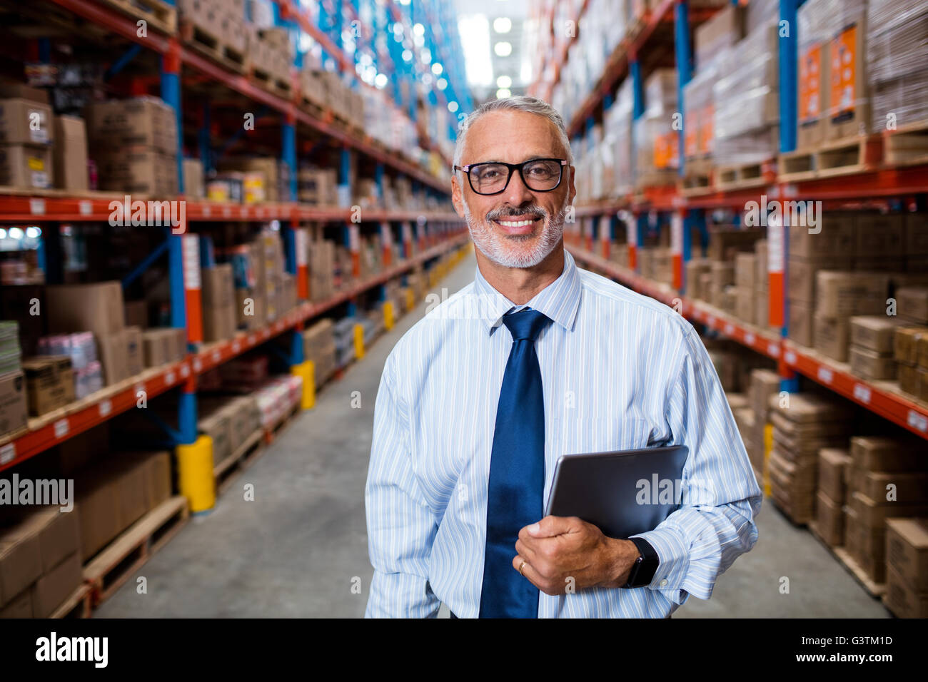 Half length of warehouse manager holding his tablet computer - Stock Image