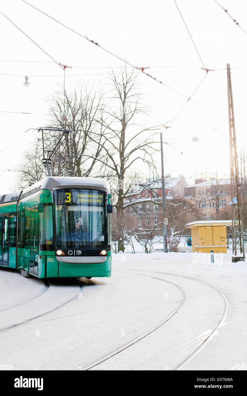 Finland, Helsinki, Ullanlinna, Trams on street in winter - Stock Image