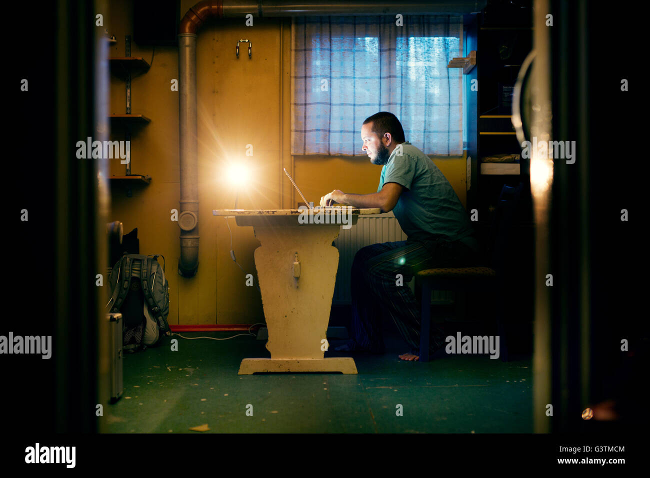 Finland, Man sitting at table and using laptop - Stock Image
