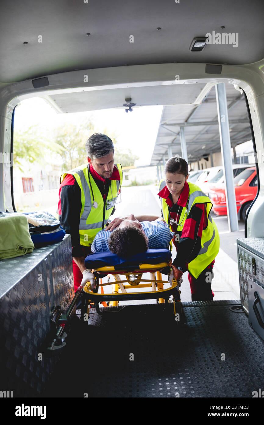 Injured man with ambulance men - Stock Image