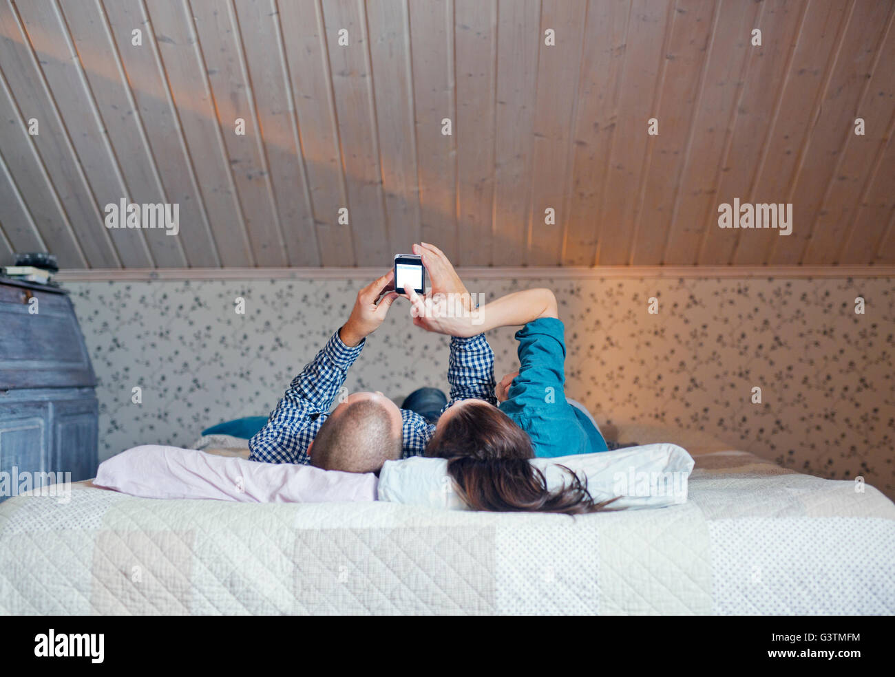 Finland, Couple lying on bed and using smart phone - Stock Image