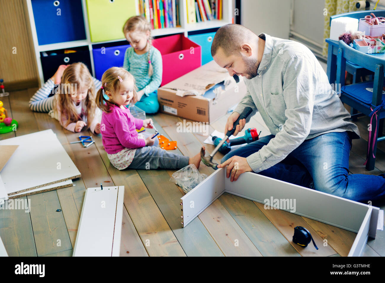 Finland, Father building cabinet for daughters (12-17 months, 2-3) in nursery - Stock Image