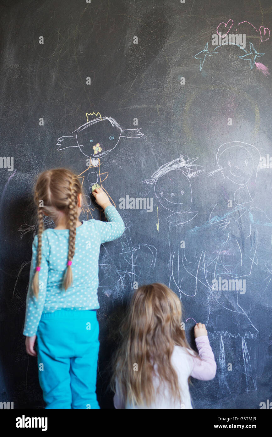 Finland, Sisters (12-17 months, 4-5) drawing on chalkboard - Stock Image