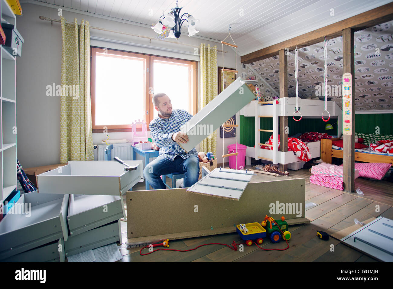 Finland, Man building cabinet in nursery - Stock Image