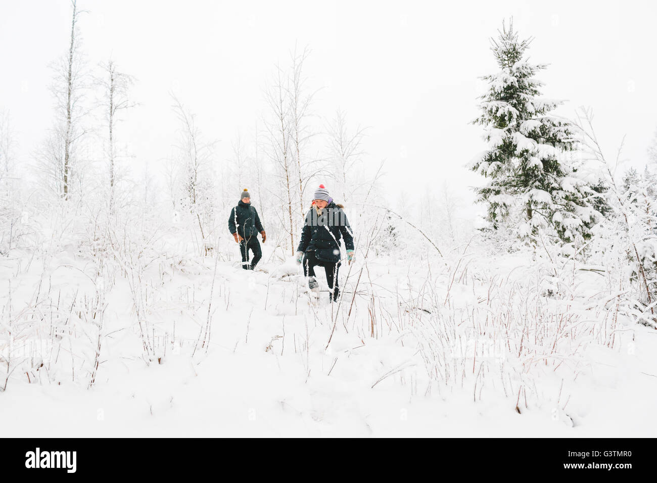 Finland, Jyvaskyla, Saakoski, Young couple walking among bare trees in winter - Stock Image