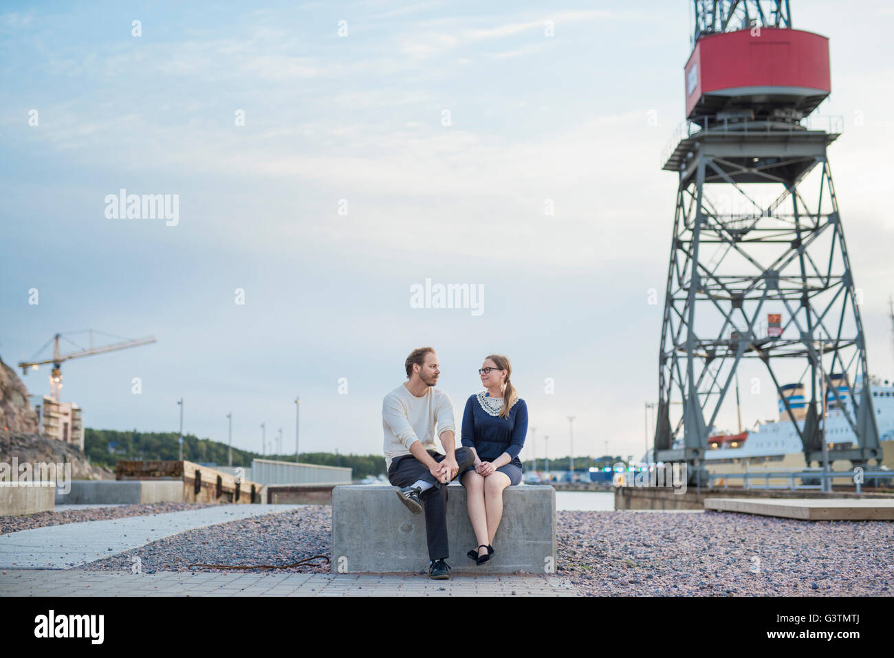 Finland, Varsinais-Suomi, Turku, Couple sitting on block and talking at construction site - Stock Image