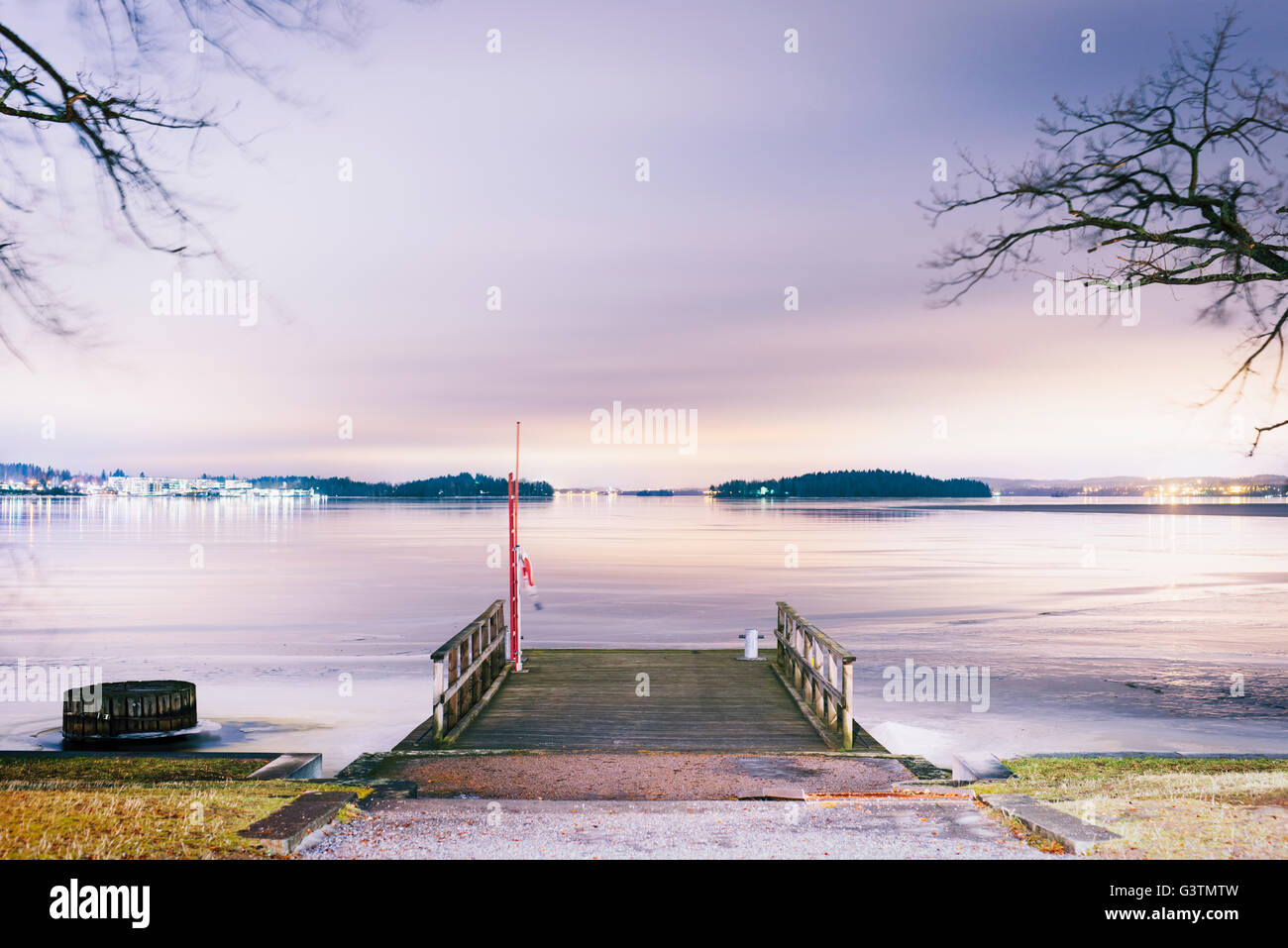 Finland, Pirkanmaa, Tampere, Pyhajarvi, Wooden jetty over lake at dusk - Stock Image