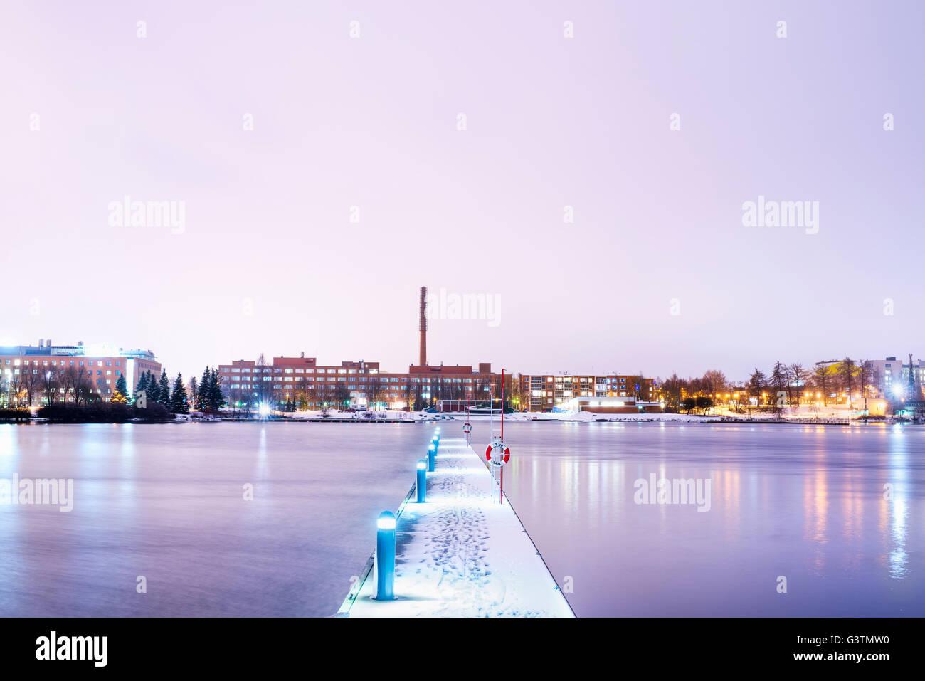 Finland, Pirkanmaa, Tampere, Pyhajarvi, Illuminated pier over lake at dusk - Stock Image