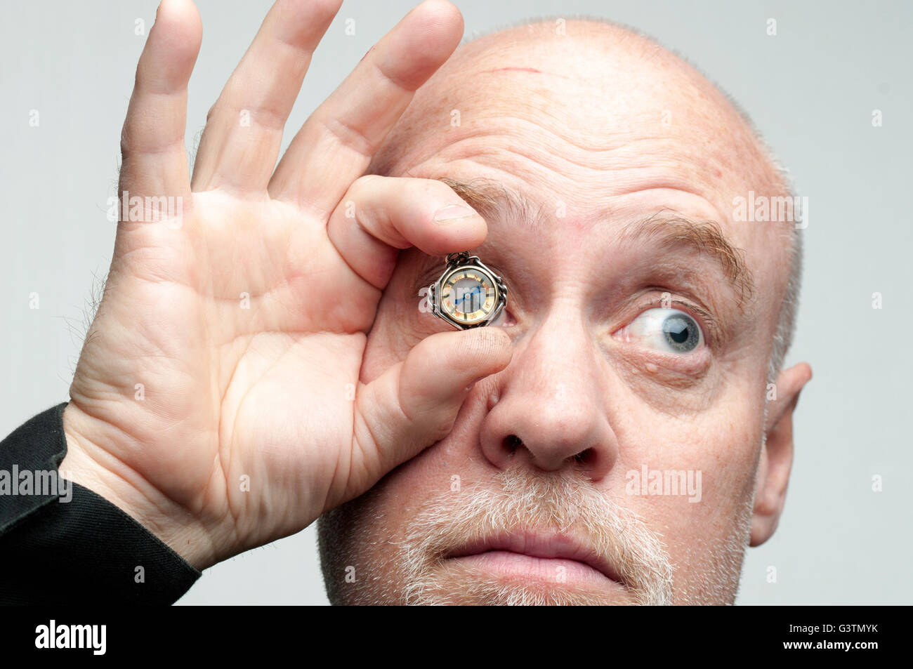 Close up of 1 person, man, with antique compass as a feature, placed over one eye - Stock Image