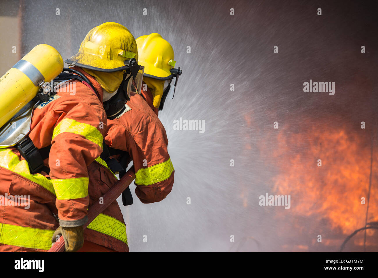 2 firefighters spraying water fire fighting operation - Stock Image