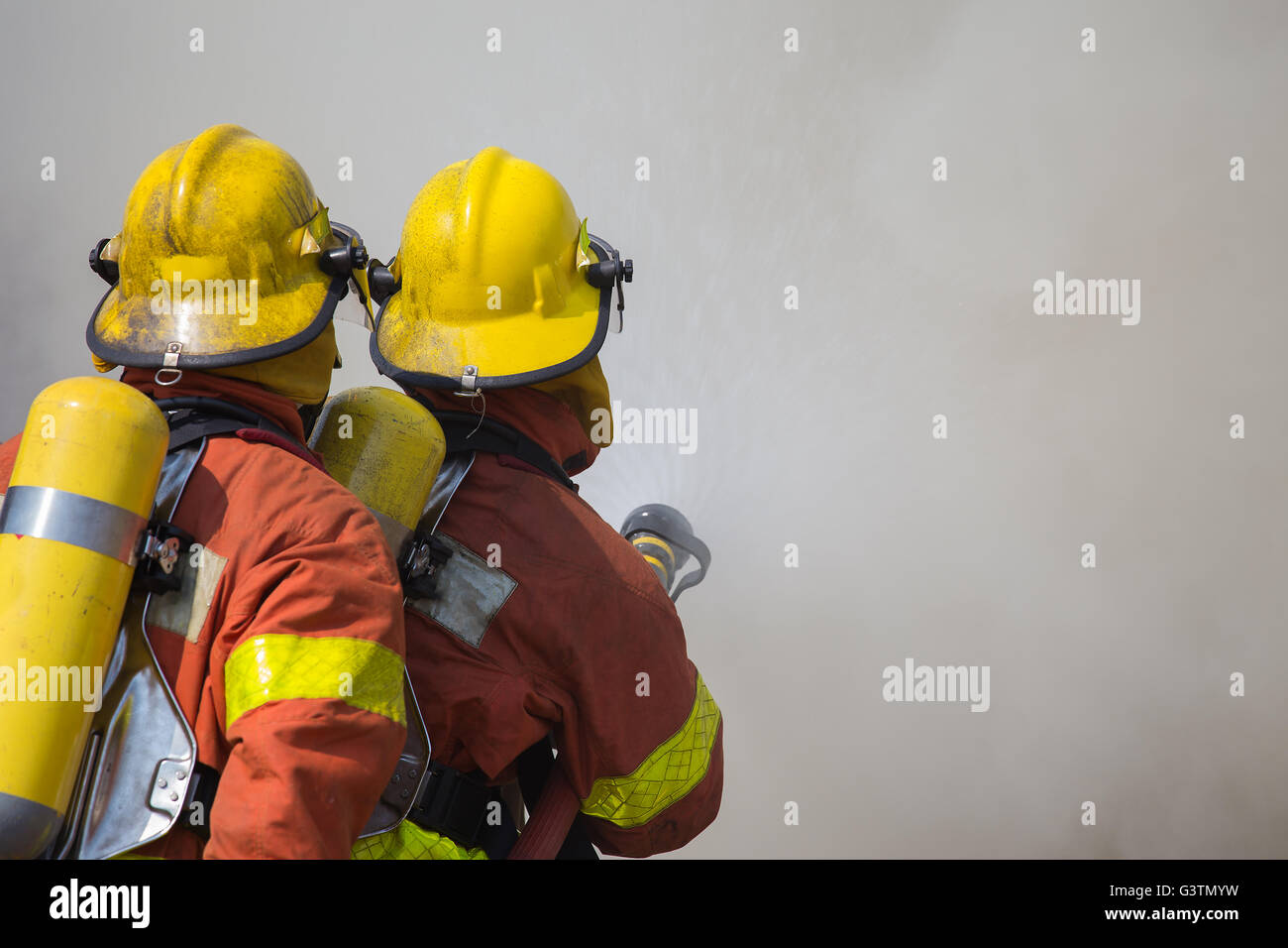 2 firemen spraying water in fire fighting with fire and dark smoke background - Stock Image